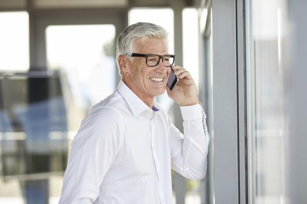 empresario de sucesso usando smartphone falando