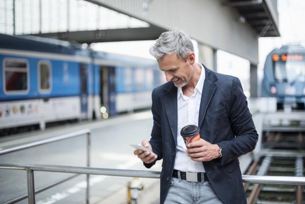 empresario segurando cafe usando telefone inteligente