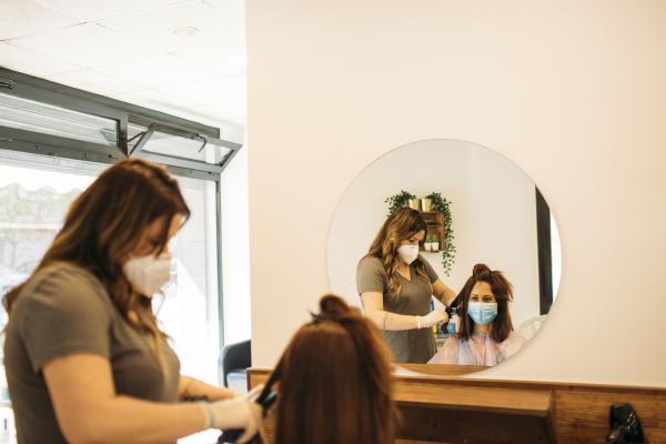 cabeleireira feminina com mascara usando maquina