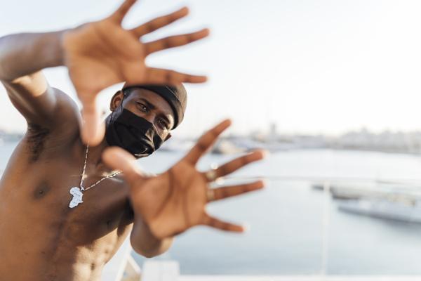 homem negro com gorro e mascara