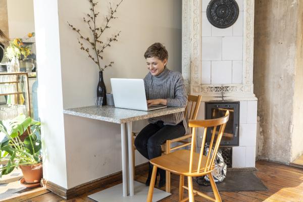mulher linda sorridente usando laptop enquanto