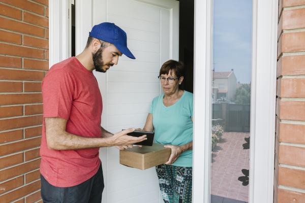funcionario dos correios mostrando tablet digital