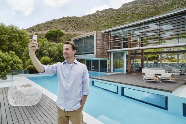 homem maduro tirando selfie no telefone