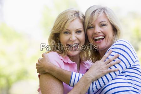 duas mulheres que abracam e que