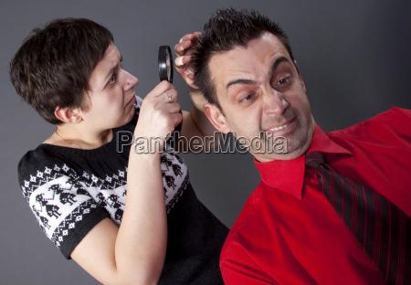 mulher examinando o cabelo masculino