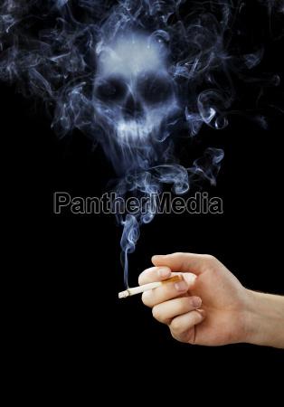 mao segurando um cigarro com fumo