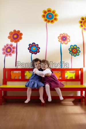 two little girls smile and hug