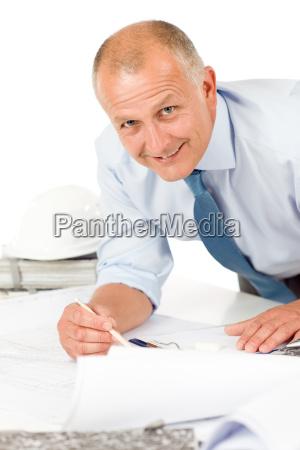 senior man work on blueprints construction