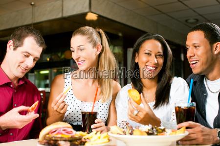 amigos comendo hamburguer e beber coca