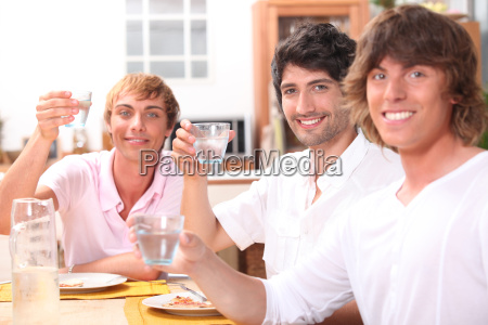 three young men eating a meal