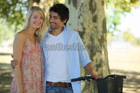 casal bonito no parque com bicicleta