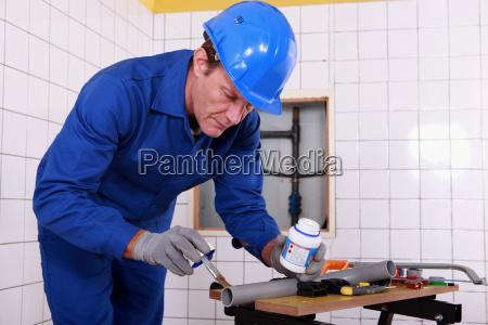 canalizador aplicando cola a um tubo