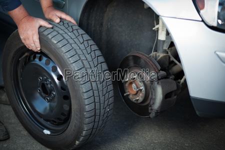 mecanico mudando uma roda de um