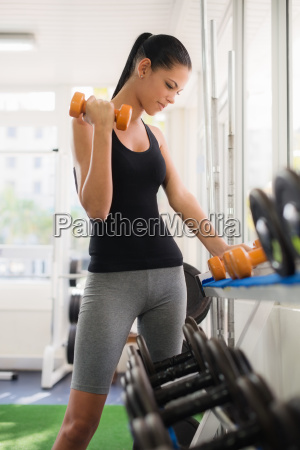 young latina woman taking weights from