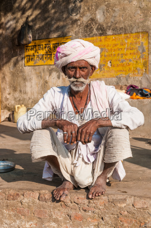 an old indian man sitting with
