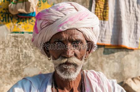 um homem indiano assentado idoso com