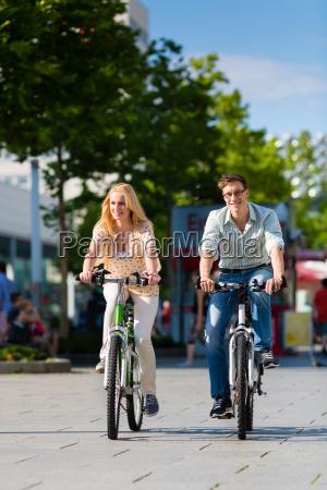 casal na cidade anda de bicicleta