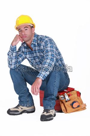 construtor furado sentado na ferramenta caixa