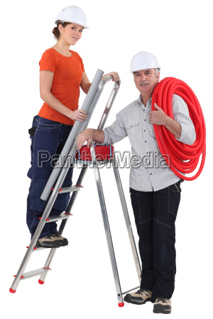 female plumber on ladder with male