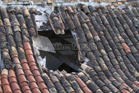 grande buraco no telhado de telha