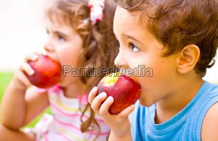 criancas felizes que comem a maca