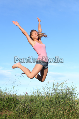 blonde teenager girl jumping happy in