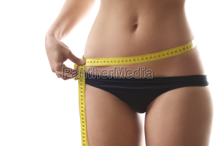 woman measuring waist with tape on