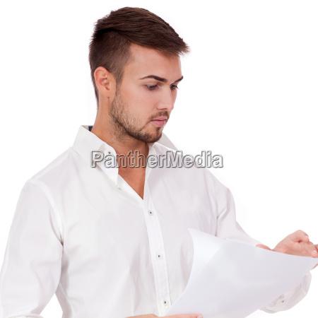 jovem empresario adulto le um documento