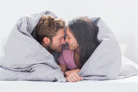 casal enrolado no edredom