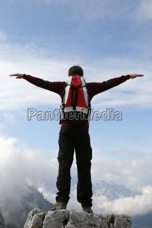 um alpinista abre os bracos para