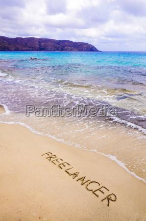 palavra freelancer escrita na areia em