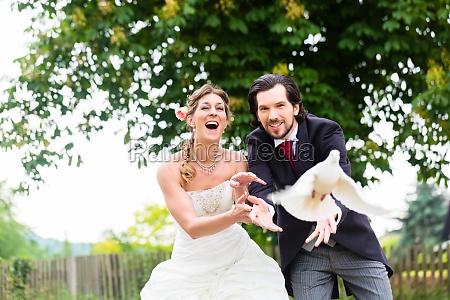 newlyweds com pombas brancas de voo