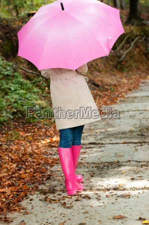 young woman with umbrella walking through