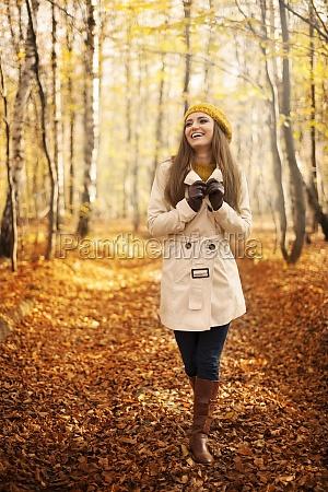 smiling woman walking in park at