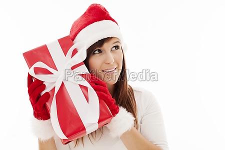 beautiful woman shaking christmas present