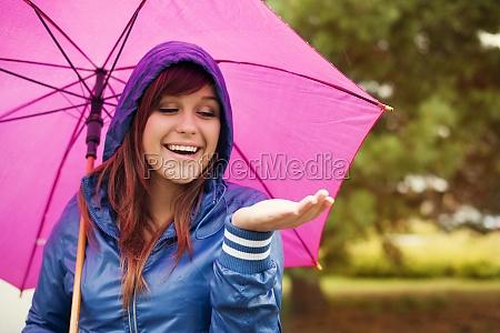 cheerful woman under pink umbrella checking