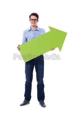 smiling man holding green arrow