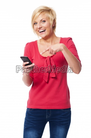 laughing woman pointing on mobile phone