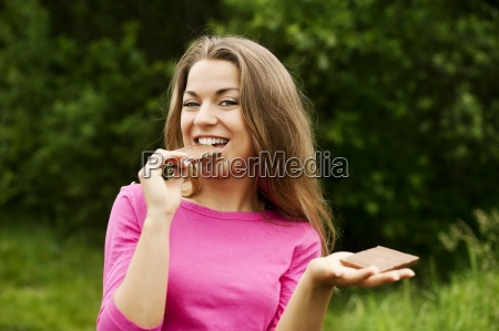 young woman eating chocolate in forest