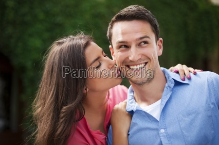 young woman kissing her boyfriend on