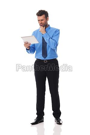 businessman holding digital tablet and grimacing