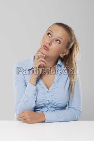 thinking and pensive woman sitting at