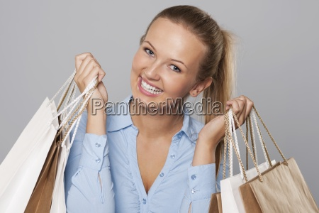 satisfied blonde woman holding shopping bags