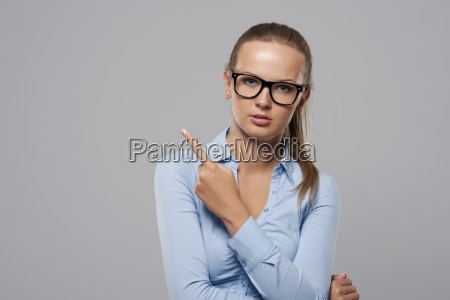 serious woman wearing fashion glasses pointing