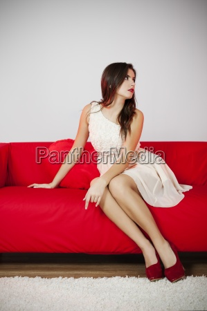 elegant woman sitting on red sofa
