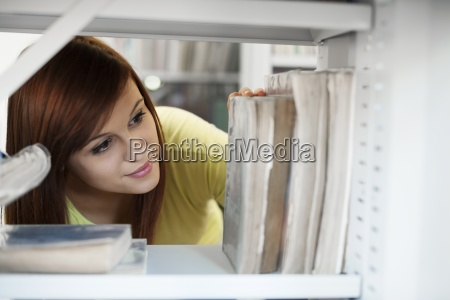 beautiful student selecting book in library