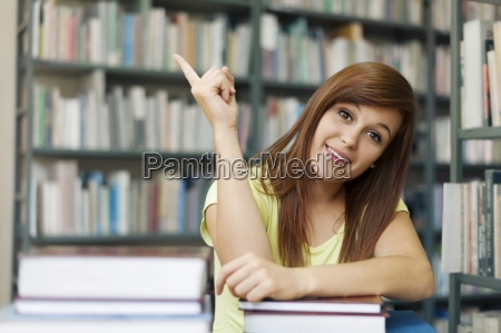 beautiful student pointing at copyspace
