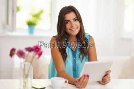smiling woman using digital tablet at