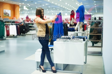 attractive woman choosing cloths in shop