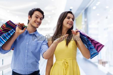 smiling man showing something woman in